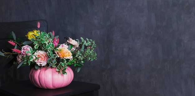 Autumn floral bouquet in colored pumpkin vase on black chair, ba
