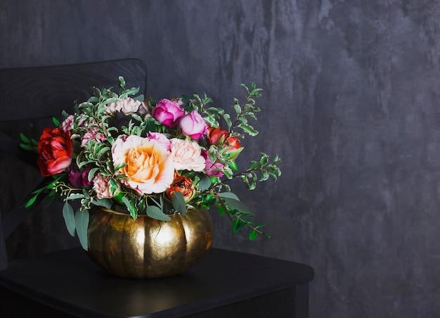 Autumn floral bouquet in colored pumpkin vase on black chair, co