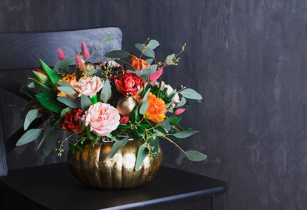 Autumn floral bouquet in colored punpkin vase on black chair, co