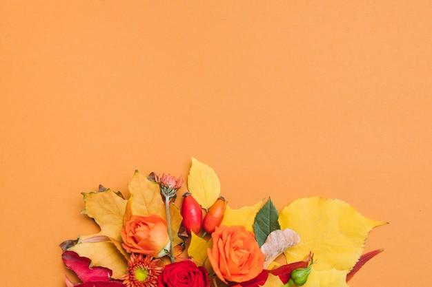 Осенний цветочный букет осенние ягоды, разноцветные листья и розы на оранжевом