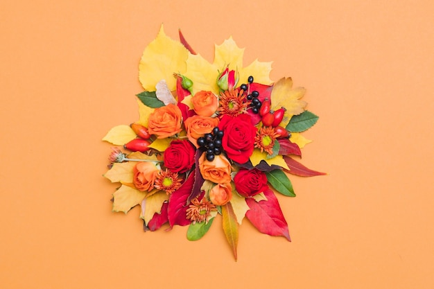 Autumn floral bouquet fall berries, colorful leaves and roses on orange