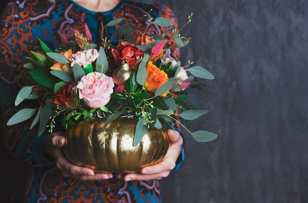 Autumn floral bouquet in pumpkin vase. decoration of flowers in