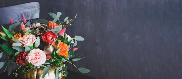 Autumn floral bouquet in punpkin vase on black chair, banner