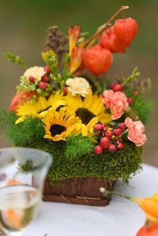 Autumn floral bouquet with sunflowers and physalis vase for halloween