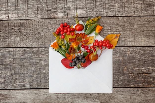 Осенняя цветочная композиция. растения калины рябины ягоды шиповника свежие цветы красочные листья в почтовом конверте на деревянных фоне. понятие экологии естественных растений падения. плоский вид сверху, макет