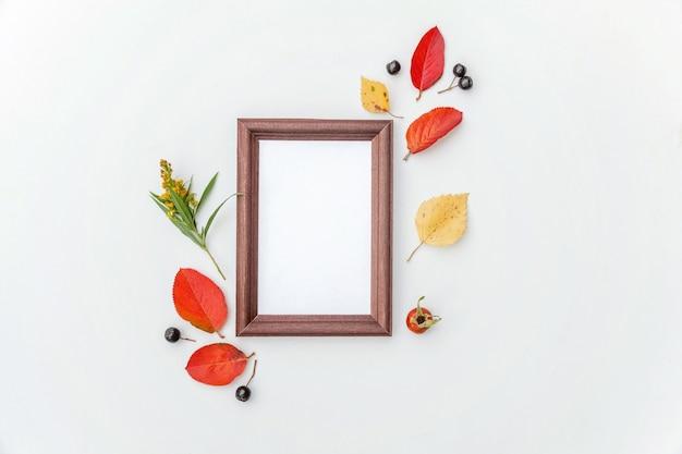 Осенняя цветочная композиция. вертикальная рамка макет черноплодной рябины ягоды красочные листья шиповника цветы на белом фоне. понятие экологии естественных растений падения. плоский вид сверху, копия пространства