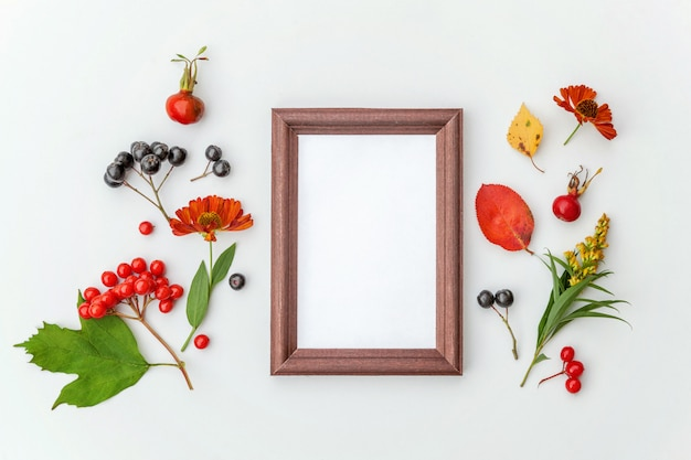 Autumn floral composition. vertical frame mockup chokeberry rowan berries colorful leaves dogrose flowers