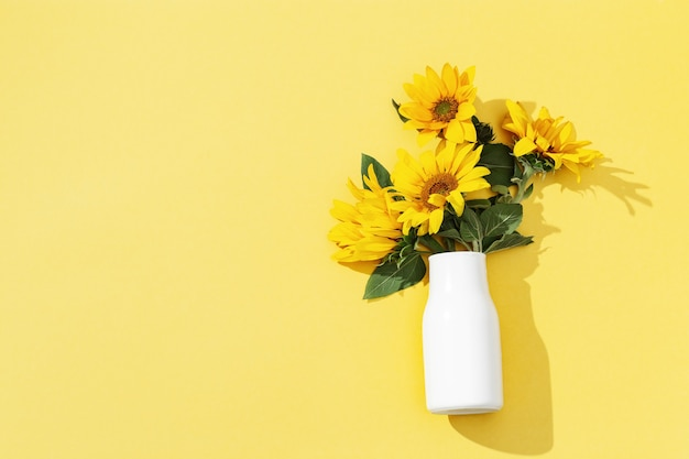 黄色い表面に白い花瓶にひまわりの秋の花