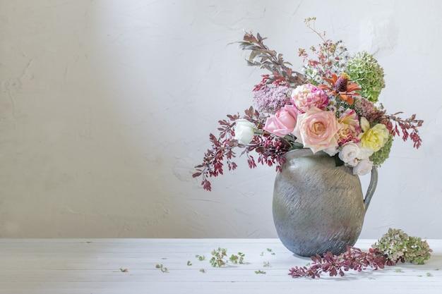 背景の白い壁に素朴なセラミックの水差しの秋の花とベリー