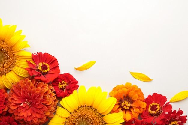 灰色の背景、上面図にひまわり、葉、花で作られた秋のフラワーアレンジメント。クリエイティブな構成。上面図