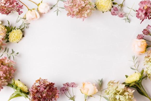 가 꽃 구성입니다. 분홍색 장미, 흰색 회색 배경에 수국 꽃으로 만든 프레임. 평평한 평지, 평면도, 복사 공간.