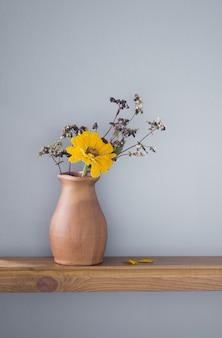 背景の灰色の壁に素朴なセラミック花瓶の秋の花