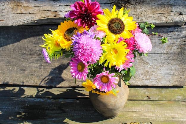 木製の背景に素朴な粘土の水差しの秋の花