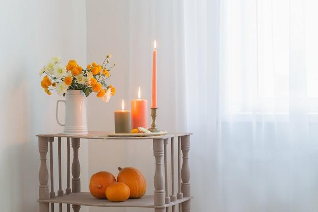 ヴィンテージの木製棚に燃えるろうそくとカボチャと秋の花