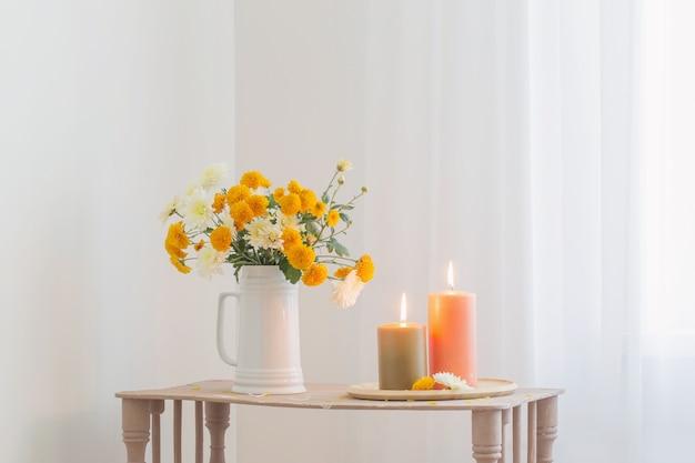 ヴィンテージの木製棚に燃えるろうそくと秋の花