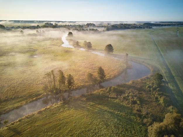 秋の霧の日の出。霧のかかった朝の夜明け。秋の田園風景。小さな川、牧草地と野原の木々