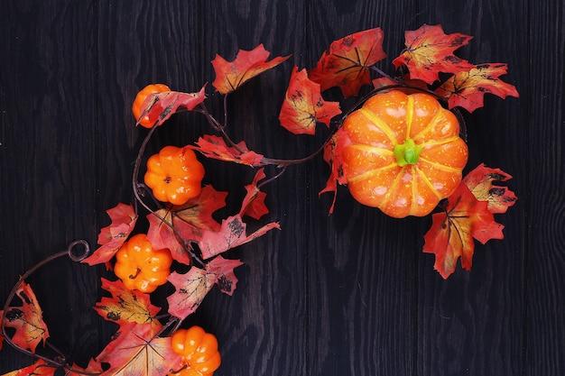 Autumn foliage with decorative pumpkins on wood.
