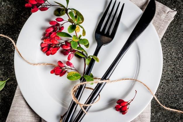 秋の食品backgorundコンセプト感謝祭のディナー暗い石のテーブルの装飾のような秋の果実とカトラリーナイフフォークのセット