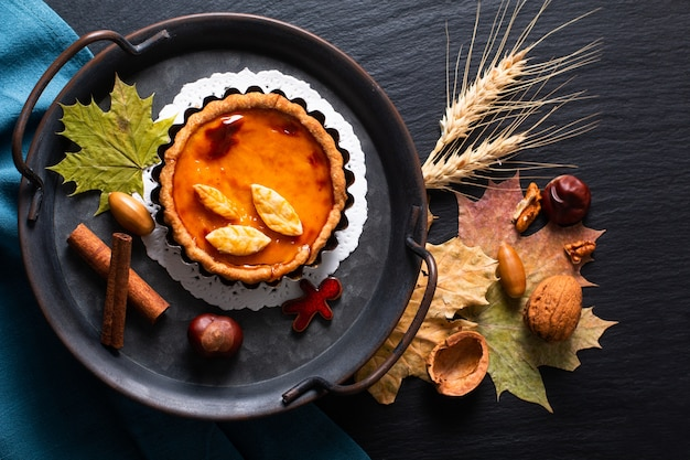 Autumn food concept homemade organic rustic pumpkins pie decorate by autumn leave on black background with copy space