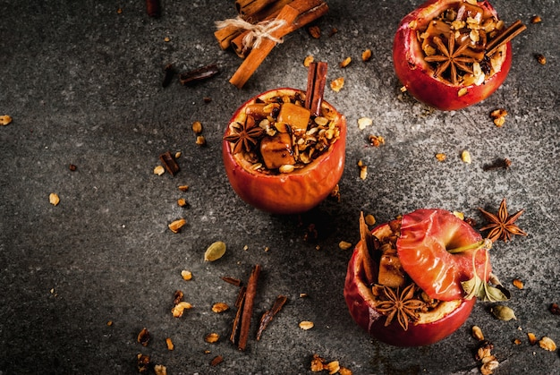 Autumn food recipes. baked apples stuffed with granola, toffee and spices. on black stone table, copyspace top view