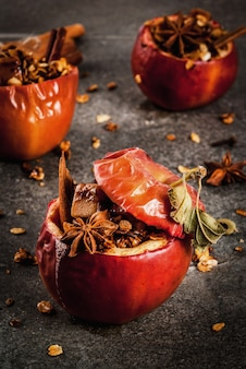 Autumn food recipes. baked apples stuffed with granola, toffee and spices. on black stone table, copyspace