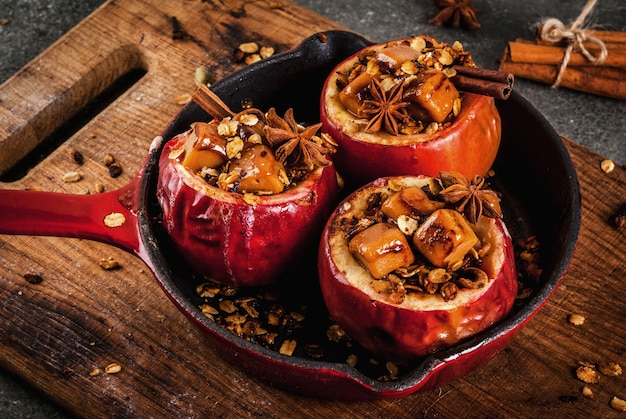 Autumn food recipes. baked apples stuffed with granola, toffee and spices. on black stone table, in frying pan, copyspace