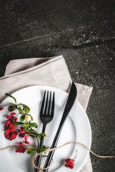 가 음식 장면 개념입니다. 추수 감사절 저녁 식사, 칼 칼 세트로 어두운 돌 테이블, 장식 처럼가 열매와 포크. 검은 장면. 복사 공간 평면도 수직