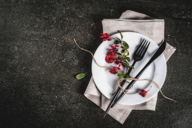 가 음식 장면 개념입니다. 추수 감사절 저녁 식사, 칼 칼 세트로 어두운 돌 테이블, 장식 처럼가 열매와 포크. 검은 장면. 복사 공간 평면도