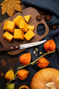 Autumn food slices on wooden board of pumpkin high view