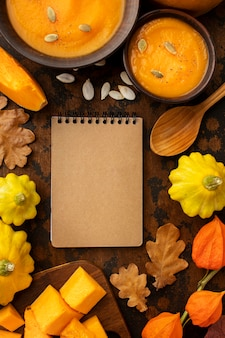 Zuppa e verdure dell'alimento di autunno con il taccuino vuoto