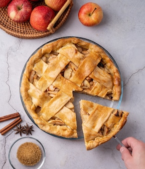 Autumn foods. top view of homemade apple pie on white wooden table, hand taking a piece of pie