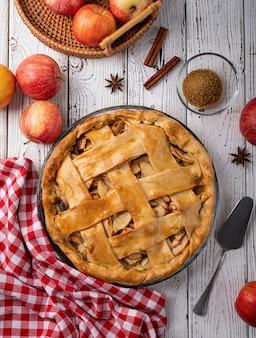 가을 음식. 사과, 설탕, 식탁보로 장식된 흰색 나무 테이블에 있는 홈메이드 사과 파이의 꼭대기 전망