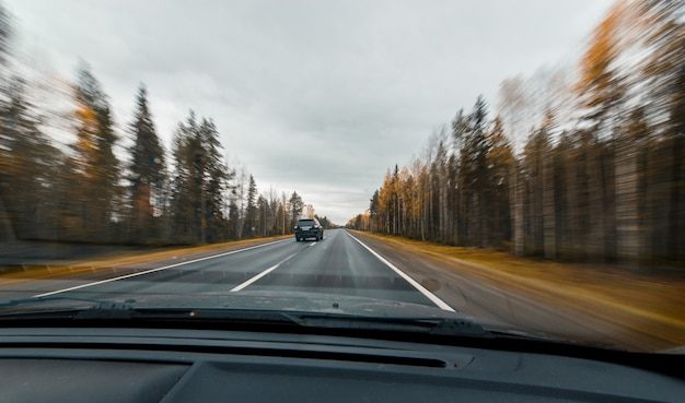 Autumn forest road at high speed drive. view from windscreen. crossover car overtakes us.