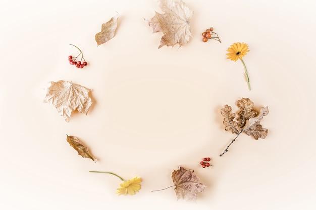 秋のフレーム。黄色の乾燥した紅葉と花からの組成