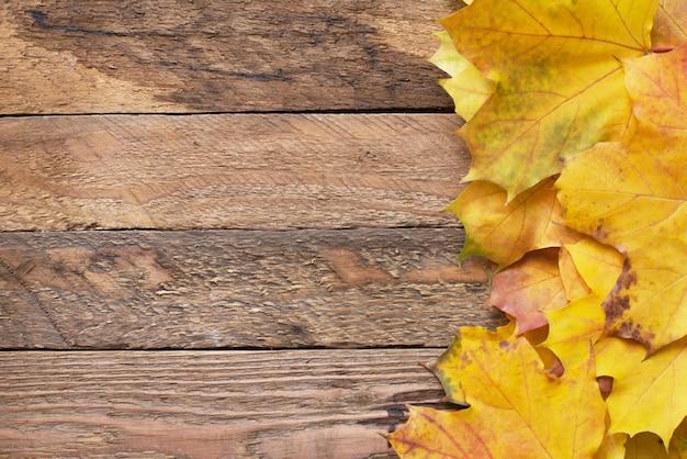 당신의 아이디어와 텍스트에 대 한 가을 프레임. 노란색, 빨간색, 주황색의 가을 낙엽 마른 잎은 갈색의 오래된 나무 판에 놓여 있습니다.