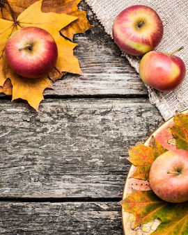 Autumn frame from apples and leaves on old wooden table. thanksgiving day concept