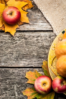 Autumn frame from apples and maple leaves on old wooden table. thanksgiving day concept