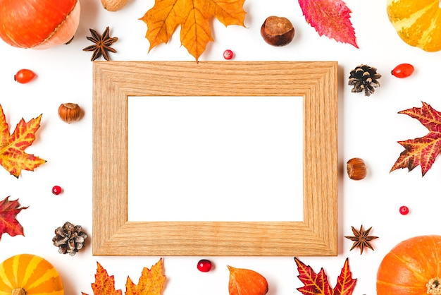 Autumn frame made of fall leaves, pumpkins, flowers, berries and nuts isolated