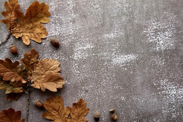 갈색 마른 잎과 도토리로 만든 가을 프레임은 어두운 콘크리트 배경에 있습니다. 템플릿 모형 가을, 할로윈. 평평한 위치, 복사 공간 배경.