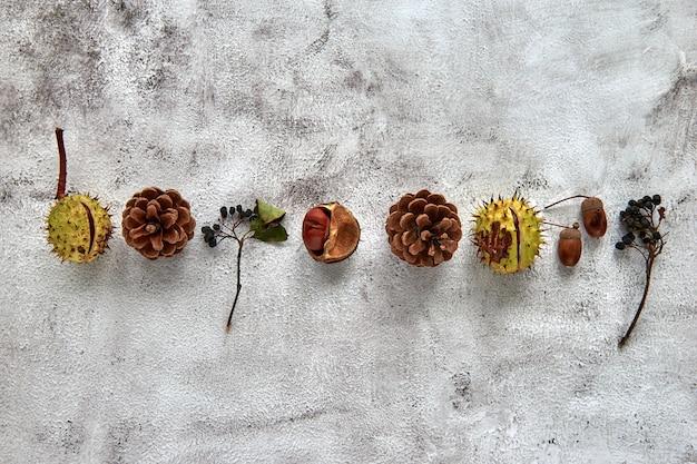 말린 잎, 나뭇가지, 솔방울, 딸기, 도토리, 손으로 만든 가을 프레임에는 어두운 콘크리트 배경에 커피 한 잔이 있습니다. 템플릿 모형 가을, 할로윈. 평평한 위치, 복사 공간 배경.