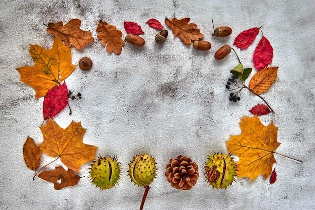 Осенняя рамка из сушеных листьев, веток, шишек, ягод, желудей и руки с чашкой кофе на темном фоне бетона. шаблон макета осень, хэллоуин. плоская планировка, копия космического фона.