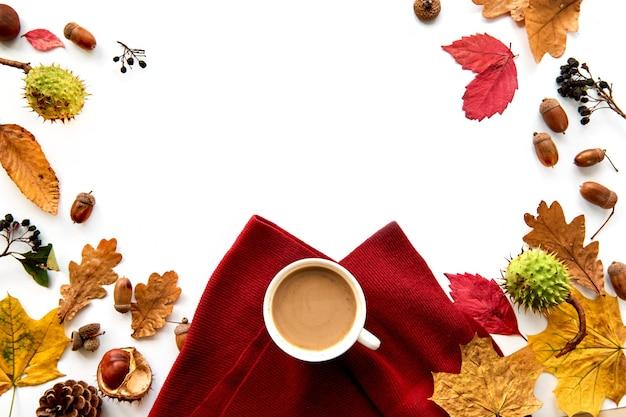 말린 잎, 솔방울, 딸기, 도토리, 따뜻한 스카프, 흰색 배경에 커피 한 잔으로 만든 가을 프레임. 템플릿 모형 가을, 할로윈. 평평한 위치, 복사 공간 배경.