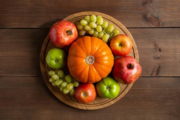 잘 익은 과일 오렌지 호박, 사과, 포도, 가닛에서 가을 프레임 정물. 둥근 나무 커팅 보드에 가을 수확과 갈색 배경이 평평하게 놓여 있습니다.