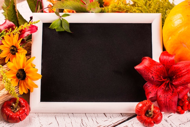 Autumn frame with flowers, vegetables and leaves. harvesting, thanksgiving day or fall concept over white wooden background.