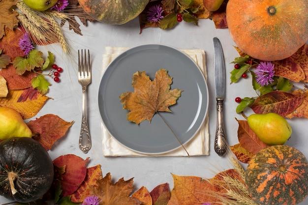 カボチャ、ナシ、葉、花、ガマズミ属の木、小麦の穂、カエデの葉が中央にある灰色のプレートと秋のフレーム。上からの眺め。