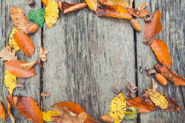 秋のフレーム。端にカラフルな葉を持つ木製のヴィンテージの背景。