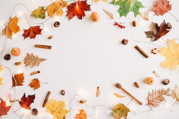 Осенняя рамка из осенних листьев и вещей на белом фоне, вид сверху