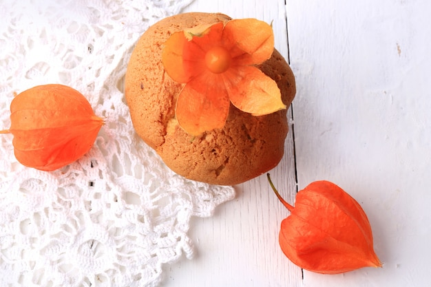 Autumn fresh homemade cupcakes with white lace cape gooseberry on wood