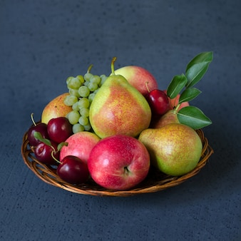 Autumn fruit mix in a wicker wooden plate.