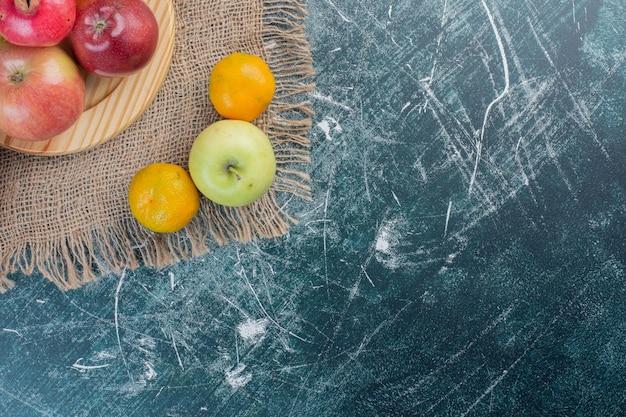 青い背景の大皿に秋の果物。